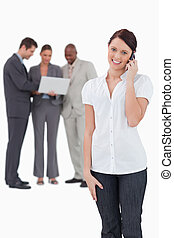 Saleswoman with associates behind her on the phone