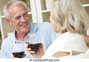 Happy Senior Man and Woman Couple Drinking Wine at Home -...