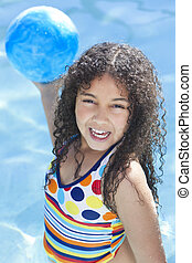 A cute happy young interracial African American girl child smiling and playing with a ball in a swimming pool