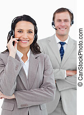 Smiling call center agents with headsets on and arms folded...
