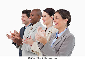 Side view of clapping sales team standing together against a...