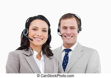 Smiling call center agents standing together against a white...