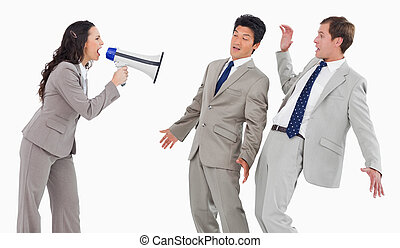 Businesswoman with megaphone shouting at colleagues against...