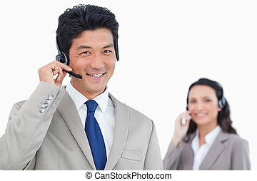 Smiling call center agent with colleague behind him