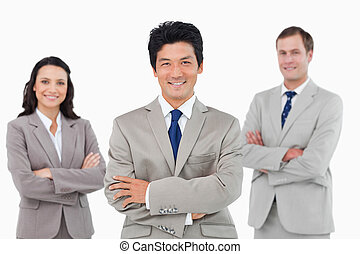 Smiling sales team with arms folded against a white...