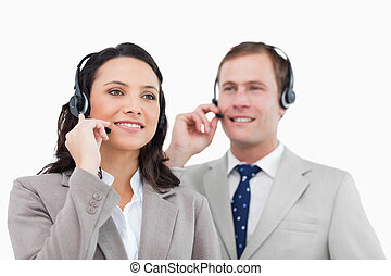 Telephone help desk employees with headsets against a white...