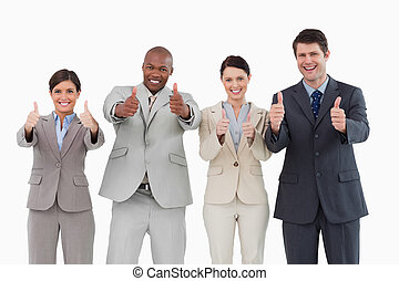 Smiling sales team giving thumbs up - Smiling sales-team...