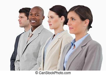 Smiling salesman standing between his associates against a...