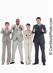 Business team giving thumbs up together against a white...