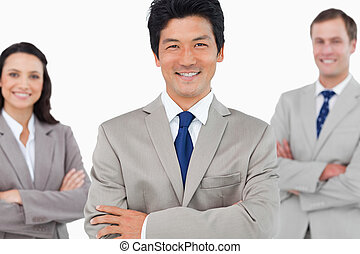 Smiling sales team with arms crossed against a white...