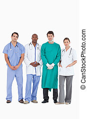 Confident medical team standing together against a white...