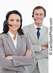 Smiling call center agents with headsets and arms folded...