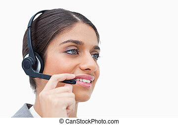 Side view of female call center agent with headset against a...