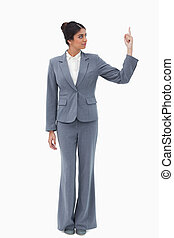 Businesswoman looking at hand while pointing up