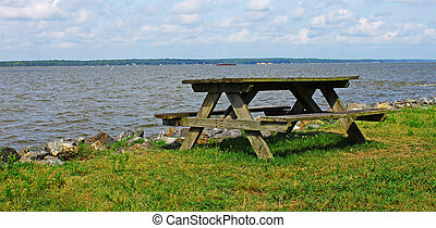 A Picnic table on a summer day along the rock lined shore of a beach along the choppy York River in Virginia with room for your text.