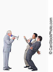Mature businessman with megaphone yelling at his employees...