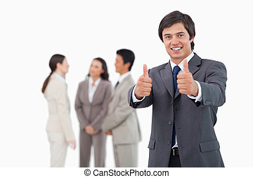 Salesman giving his approval with team behind him