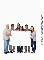 Smiling group of friends holding blank sign together against...