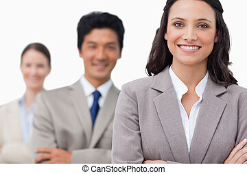 Smiling young sales team with arms folded