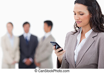 Saleswoman writing text message with colleagues behind her...