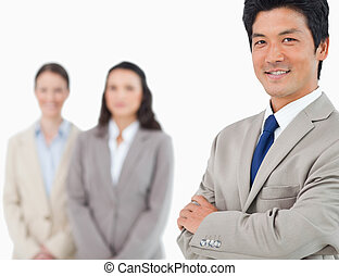 Smiling young businessman with colleagues behind him
