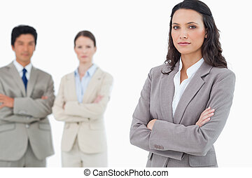 Confident saleswoman with arms folded and colleagues behind her