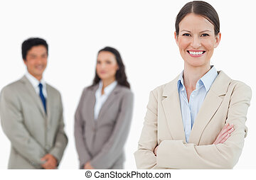 Smiling saleswoman with arms folded and associates behind her
