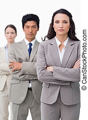 Businesswoman standing with team and folded arms
