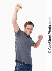 Victorious young man raising fist against a white background