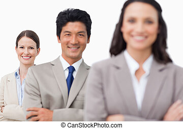 Smiling sales team standing with arms folded