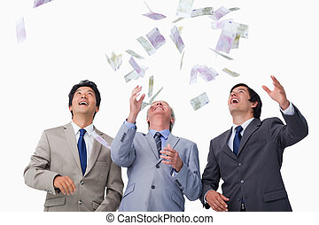 Bank notes raining down on business team against a white...