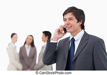 Salesman talking on cellphone with colleagues behind him...