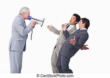 Senior salesman with megaphone yelling at his employees