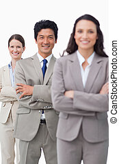 Smiling sales team standing with folded arms