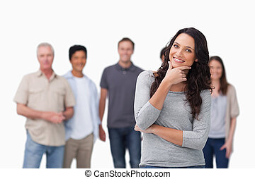 Smiling woman in thinkers pose and friends behind her...
