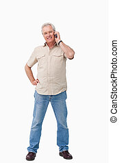 Smiling mature male talking on his cellphone against a white...