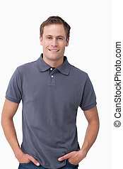 Smiling young male with hands in his pockets against a white...