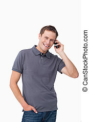 Smiling young man on his mobile phone against a white...