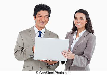 Smiling sales team with laptop