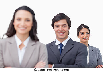 Smiling young sales team standing together with folded arms