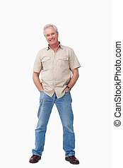 Mature male with hands in his pockets against a white...