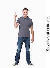 Smiling young man pointing up
