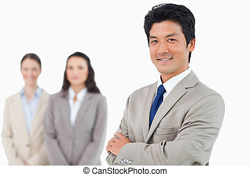 Confident smiling businessman with his team behind him