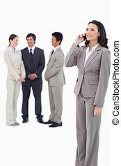 Saleswoman on the cellphone with team behind her