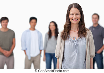 Smiling woman with friends standing behind her against a...