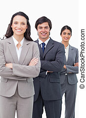 Smiling young sales team standing together with arms folded