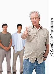Senior man giving thumb up with young people behind him