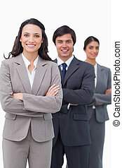 Smiling young saleswoman with her team and arms folded