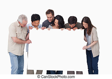 Group looking at blank sign in their hand against a white...