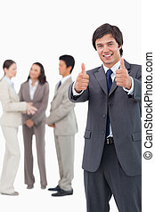 Salesman giving thumbs up with team behind him against a...